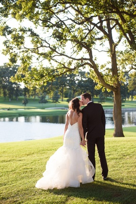 bride in monique lhuillier mermaid wedding dress and groom in gibeon tolbert kiss golf course