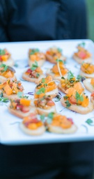 Cocktail hour appetizers of crostini with heirloom tomatoes pased by server on white tray