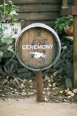 "Finger point sign with ""Ceremony"" wording on wine barrel for rustic wedding"