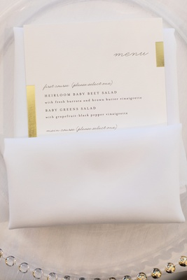 wedding menu tucked into napkin with accents of gold on border