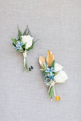 two boutonnieres with white roses and small blue flowers