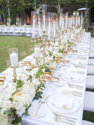 white, gold and green color scheme. tall candlebras adding warmth to dinner under the stars