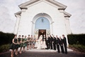 Bridesmaids and groomsmen with couple in front of church