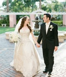 bride groom hold hands outside venue beaded gown florida wedding courtyard photo shoot veil bouquet