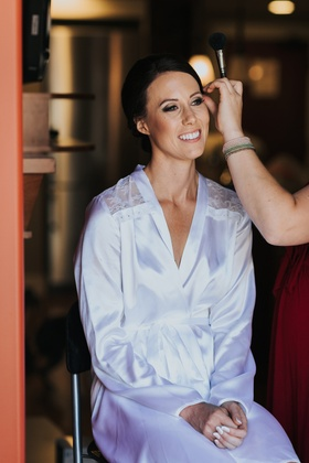 bride in white robe with lace cut outs smiles while makeup is applied