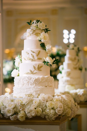 wedding cake white with ruffles flower layers gold leaves fresh roses greenery