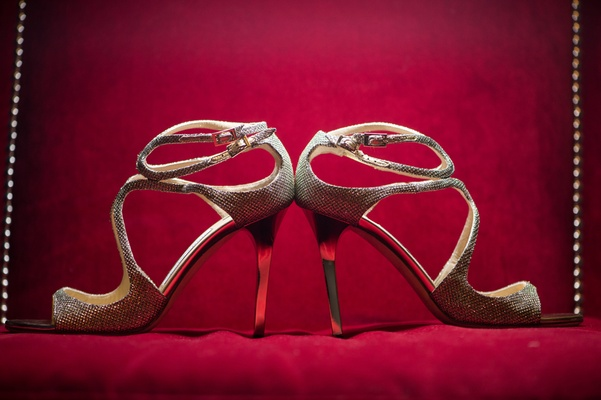 Jimmy Choo bridal shoes displayed against a red backdrop
