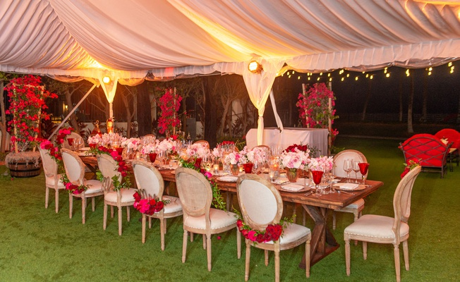 wedding reception wood table chairs pink red rose garlands low centerpiece red glassware