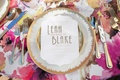 white and gold calligraphy on white paper white china gold detailing pink floral table linen