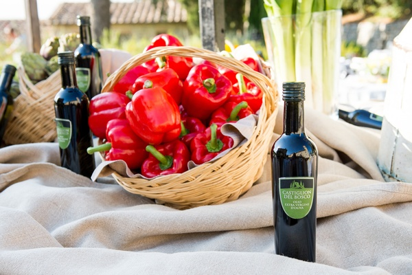 Table decorated with bright red bell peppers in a basket and bottles of olive oil