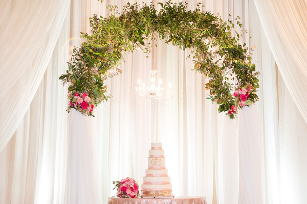 wedding cake table with chandelier and greenery arch overhead white drapery pink flowers