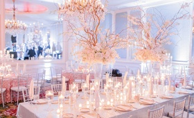 Long wedding reception table with sequined linens, ivory flowers, curly willow, candles