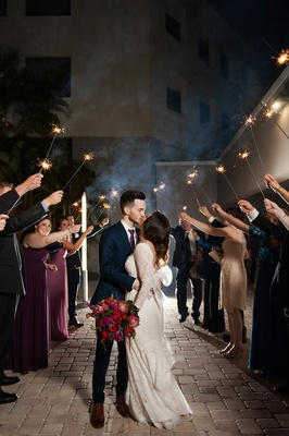 Bride and groom kissing under tunnel of sparklers