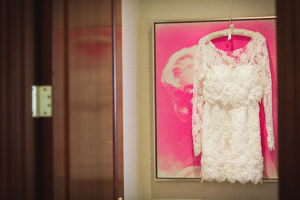 Second wedding dress hanging on pink painting white lace long sleeve scallop hem short dress