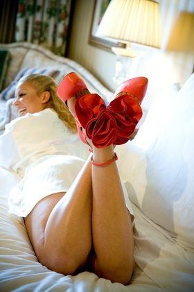 Bold red pumps with red fabric flower and ankle strap