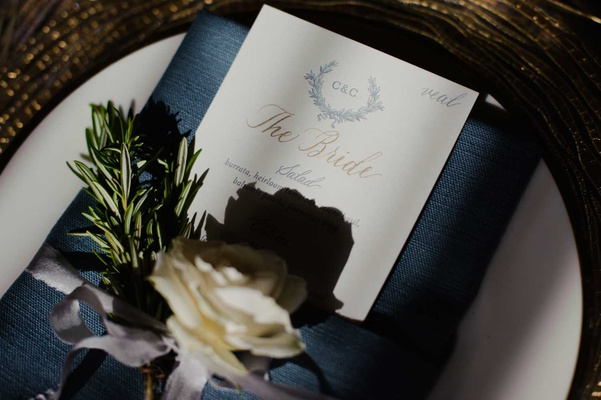 wedding reception place setting dark blue napkin white rose herb spring menu with calligraphy names