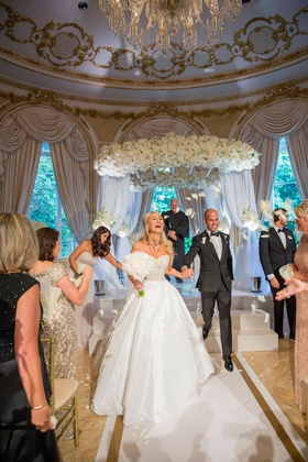 Bride in strapless Reem Acra wedding dress and groom holding hands walking on white gold aisle