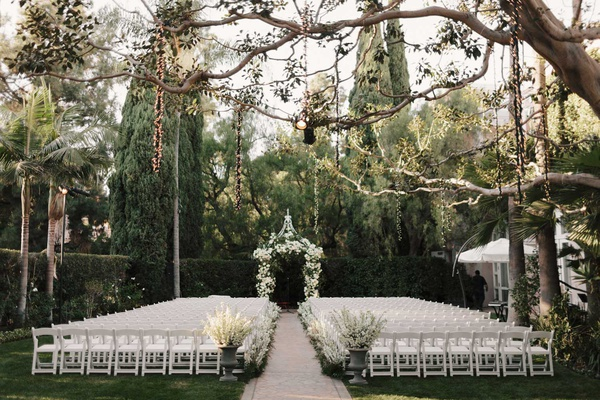 wedding ceremony white chairs urns white flowers lights hanging from tree beverly hills ceremony