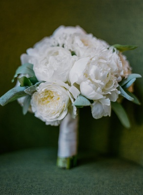 bouquet of white peonies wrapped in white ribbon