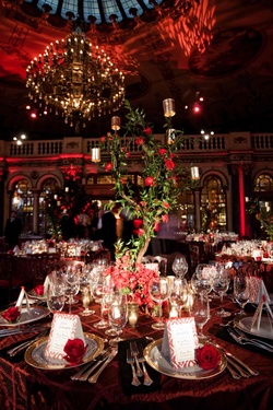 Red tablecloth with tree centerpiece and red flowers