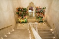 Candles on steps and floral walls next to gold mirror