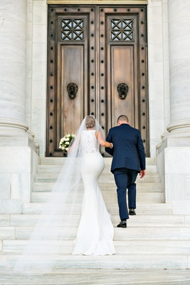 Bride in form fitting wedding dress lace back bateau neck long veil cathedral up steps washington dc