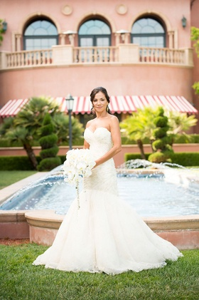 bride in mermaid romona keveva wedding dress stands in front of fountain at the grand del mar