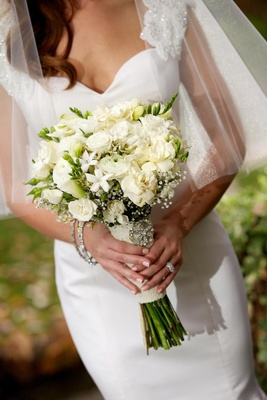 White bridal flowers wrapped in lace with brooch