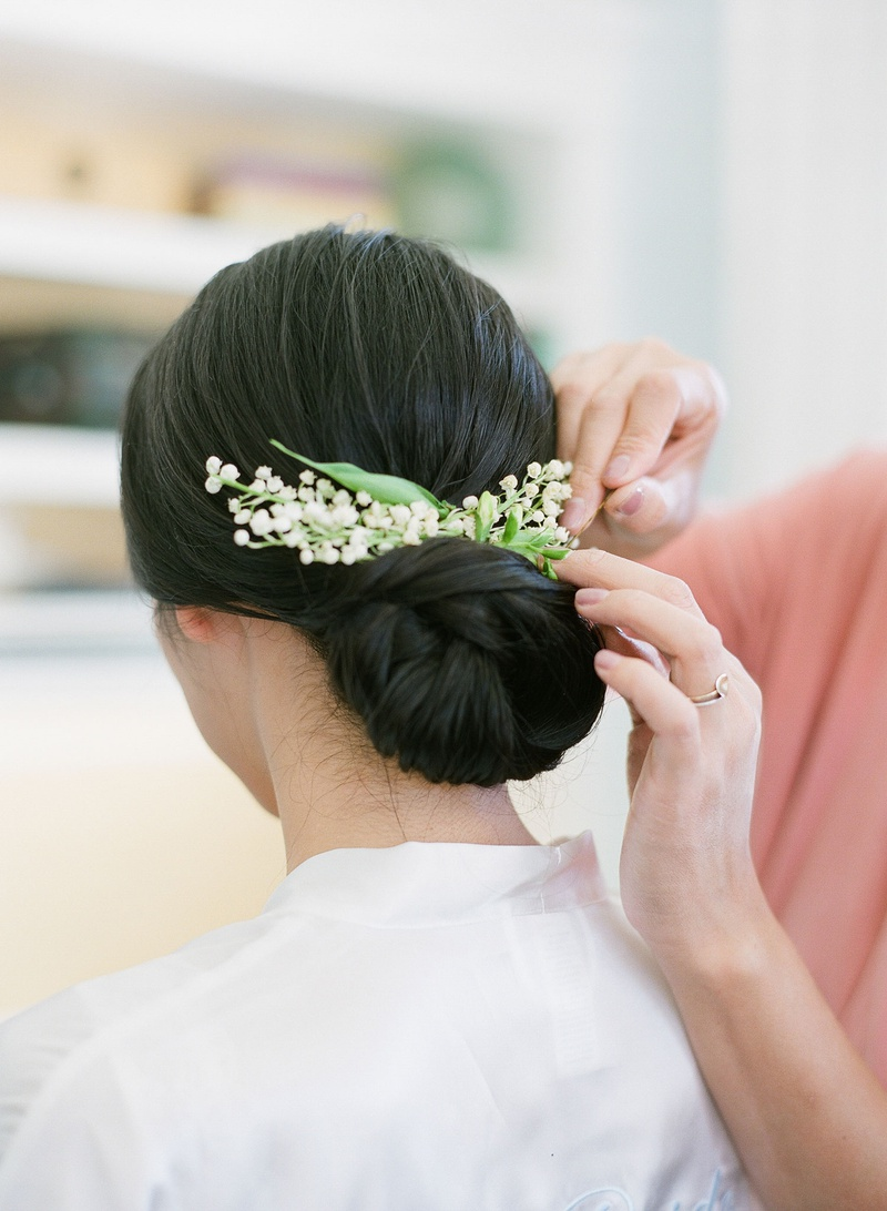 bride with low chignon hairstyle low bun wedding day with small lily of the valley blooms headpiece