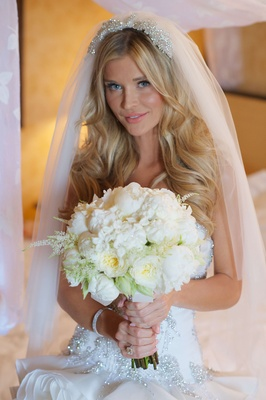 Celebrity bride holds white wedding bouquet