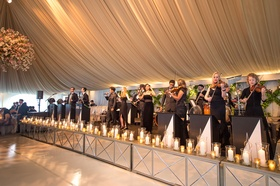 Heavily draped ballroom with large live band on stage mirror white dance floor flower chandelier