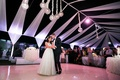 Bride in wedding dress and groom in tuxedo on dance floor with overhead lights and drapes at rooftop