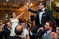 bride groom lifted by guests holding hands lively reception wedding fun dancing