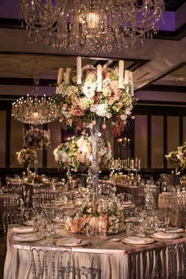 Tall glass centerpieces with flowers and candles in blush, green, white