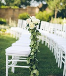 White ceremony chairs adorned with leaf garlands