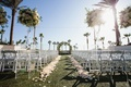 wedding ceremony facing ocean circle arch flowers by cina flower petals along grass aisle