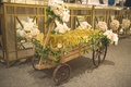 Wedding reception with a wood wagon full of flip-flops adorned with pink, white roses, greenery