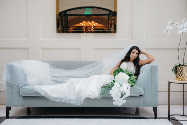 bride in maggie sottero wedding dress with silver beading lounges on slate blue couch, cathedral vei