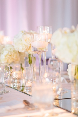 stemmed glass floating candles, mercury glass, mirrored table runner, all-white décor wedding