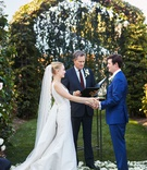 wedding ceremony outdoor white flower petal aisle greenery arch bride in updo veil groom blue suit