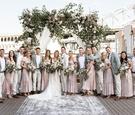 bride and groom on bridge ceremony with bohemian vintage bridesmaid dresses grey groomsmen jackets