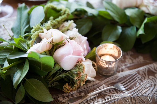 a verdant table runner featuring greenery and pink flowers rose