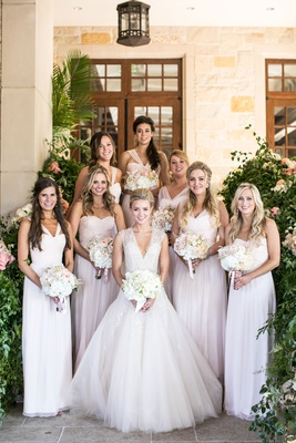 Bride and her bridesmaids smile and hold their bouquets blush bridesmaid dresses mismatched neckline
