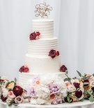 "four tiered wedding cake with fresh marsala and blush flowers, ""love you more"" cake topper"