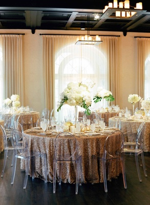 Light filled ballroom destination wedding gold sequin tables tropical centerpiece ghost chairs