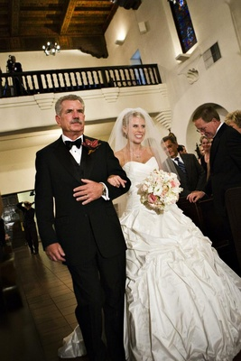 Father of bride walks bride down chapel aisle