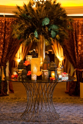 Moroccan-style engagement party table with gold vase of peacock feathers, lanterns with candles