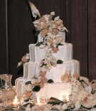 White pleated cake with peach and ivory flowers