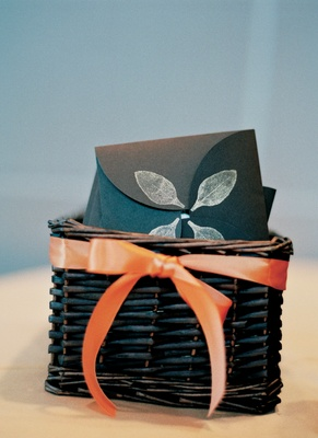 Black wedding programs decorated with white leaves