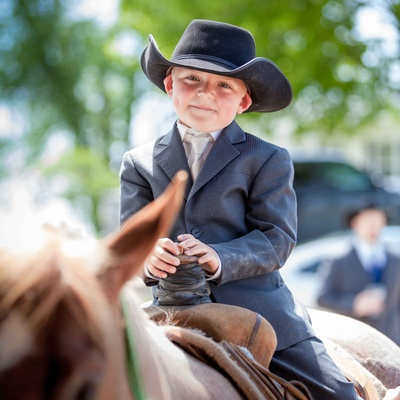 Young ring bearer boy riding Western saddle horse